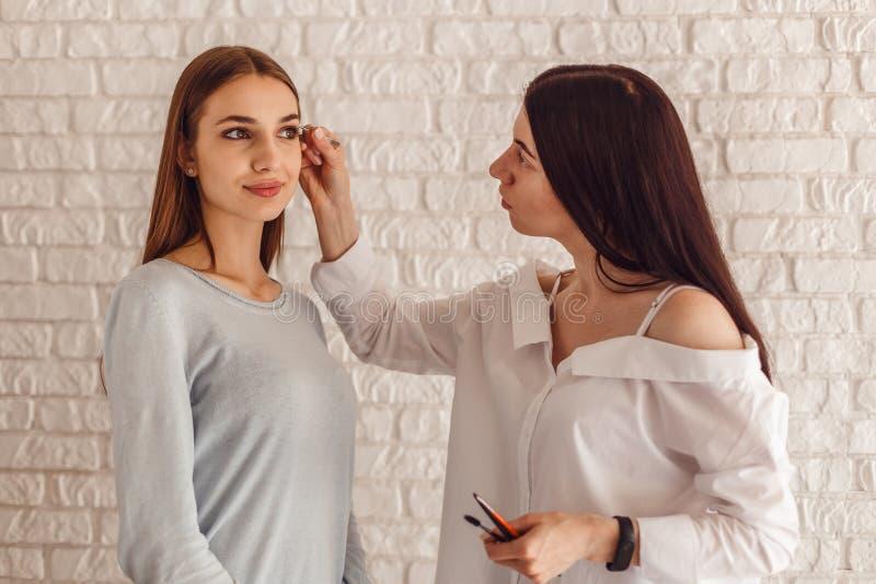 Modell- och makeupkonstnären gör en ny form naturliga ögonbryn royaltyfri bild