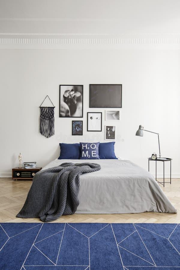 Modell på en marinblå filt och inramat fotogalleri på en vit vägg i en eklektisk sovruminre arkivfoton