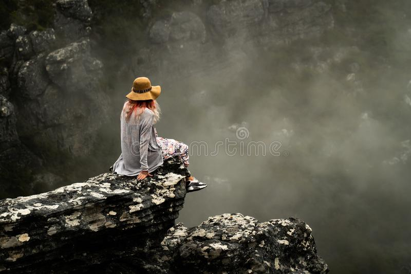 Modell saß auf Klippenrand in Cape Town lizenzfreie stockfotografie