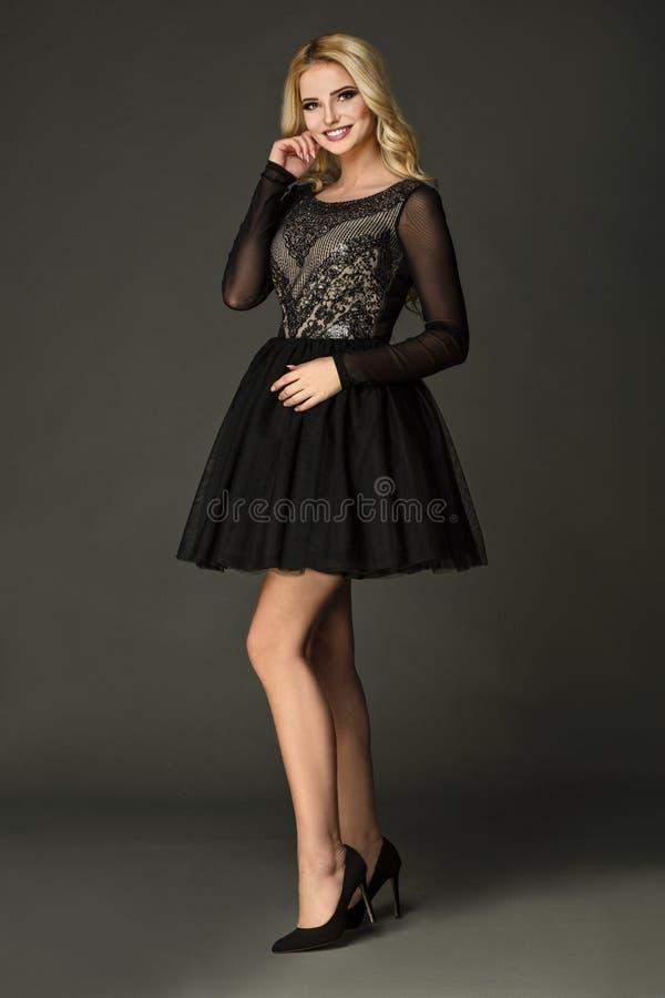 Modell som bär den svarta klänningen med att förbluffa ben arkivbild