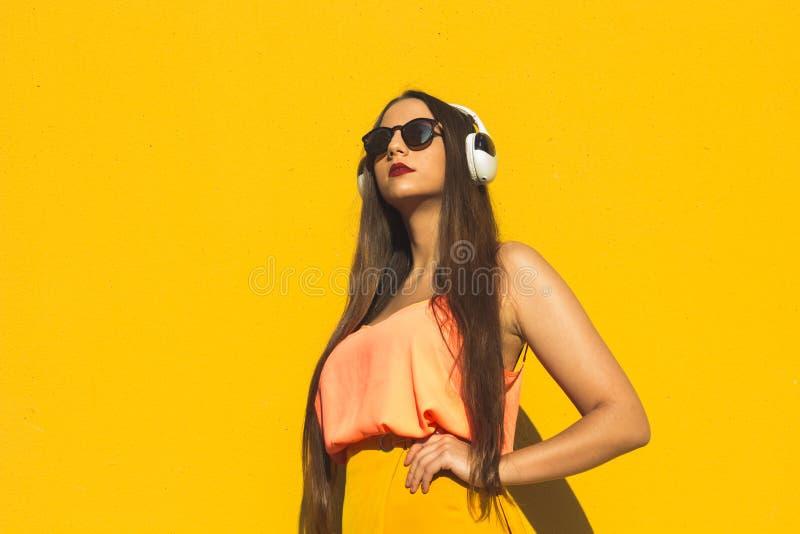 Modell som framme står solglasögon och hörlurar för en gul vägg bärande royaltyfri foto