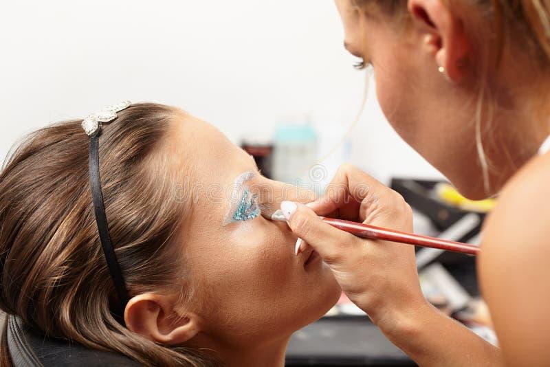 Modell som har makeup att appliceras arkivbild