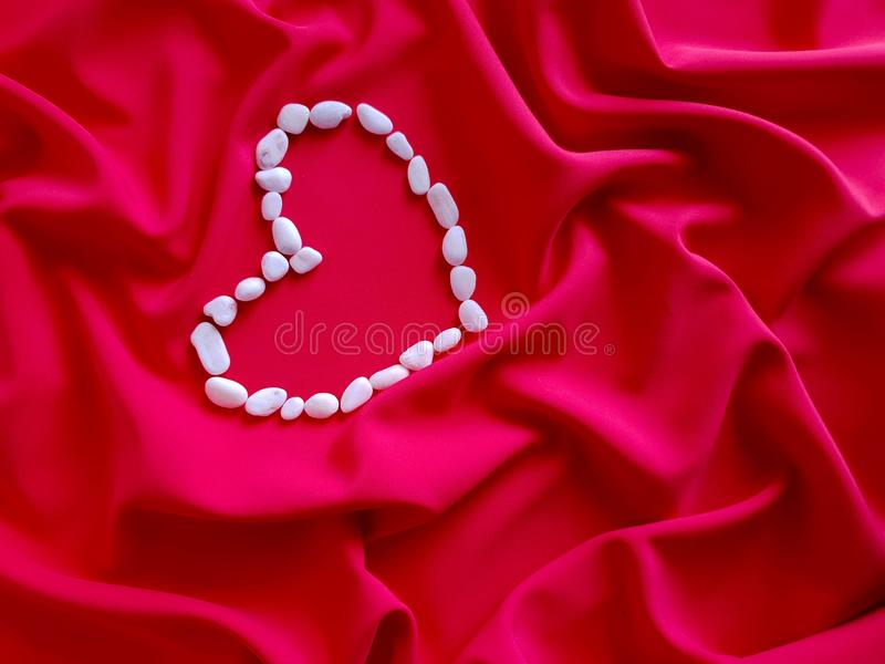 Modell textur, bakgrund, tapet Stor hjärta som göras av små vita stenar, är på bakgrunden av genomdränkt koralltyg royaltyfria foton