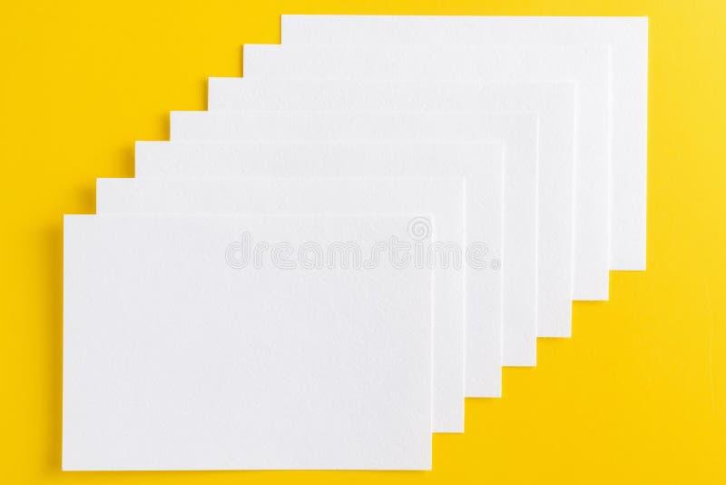 Modell von den Visitenkarten gestapelt in der Reihe auf gelbem Hintergrund stockfotografie