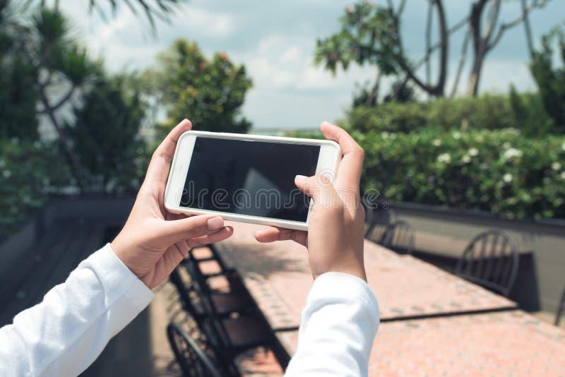 Modell von den weiblichen Händen, die frameless Mobiltelefon mit leerem Bildschirm halten und selfie am Hintergrund machen stockbild
