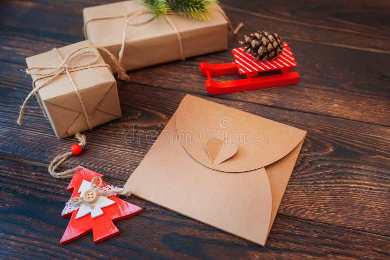 Modell-Weihnachtsleere Karte, Umschlag mit Geschenkboxen, Weihnachtselemente auf einem hölzernen Hintergrund lizenzfreie stockbilder