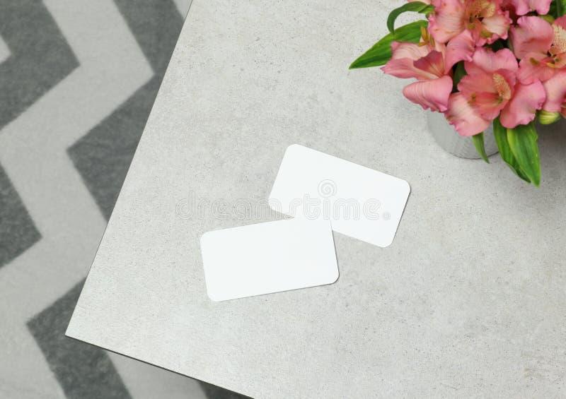 Modellaffärskortet med blommor på grå färger stenar tabellen royaltyfria bilder