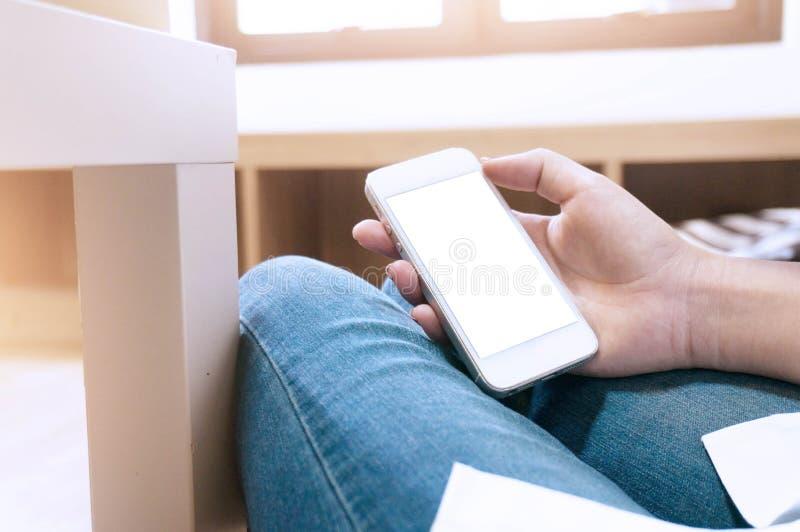 Modellbild av den hållande vita mobiltelefonen för hand med mellanrumssvart arkivfoton