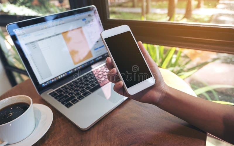 Modellbild av händer som rymmer den vita smartphonen med mellanrumssvartskärmen, bärbara datorn och kaffekoppen på trätabellen royaltyfri foto