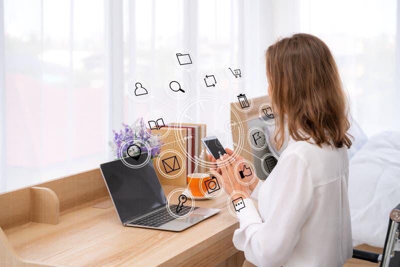 Modellbild av kvinnas händer som rymmer den vita mobiltelefonen med den tomma svarta skärmen i ljust sängrum med social massmedia arkivbild