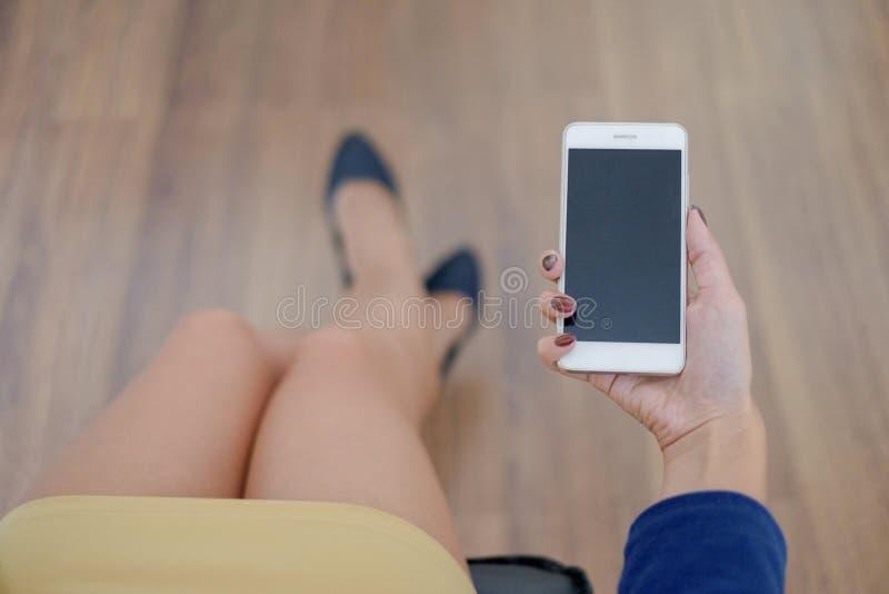 Modellbild av mobiltelefonen för hand för kvinna` s den hållande vita med den svarta skärmen på lår med trägolvbakgrund in royaltyfria bilder