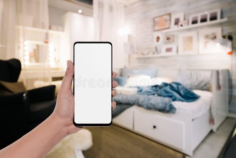 Modellbild der Hand modernen Handy mit Tischplattenschirm des leeren Kopienraumes für Ihre Anzeige im Schlafzimmer halten stockfotografie