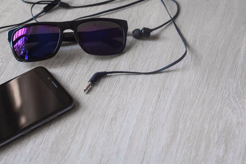 Modellbild des Schauspielnotizbuch-Bleistiftgummi-Kopfh?rermachthabers mit schwarzem Handy und leerem wei?em Schirm auf Holztisch stockfoto