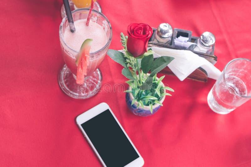 Modellbild des weißen Handys mit leerem weißem Schirm auf rotem Hintergrund im Restaurant Tropische Bali-Insel stockbilder