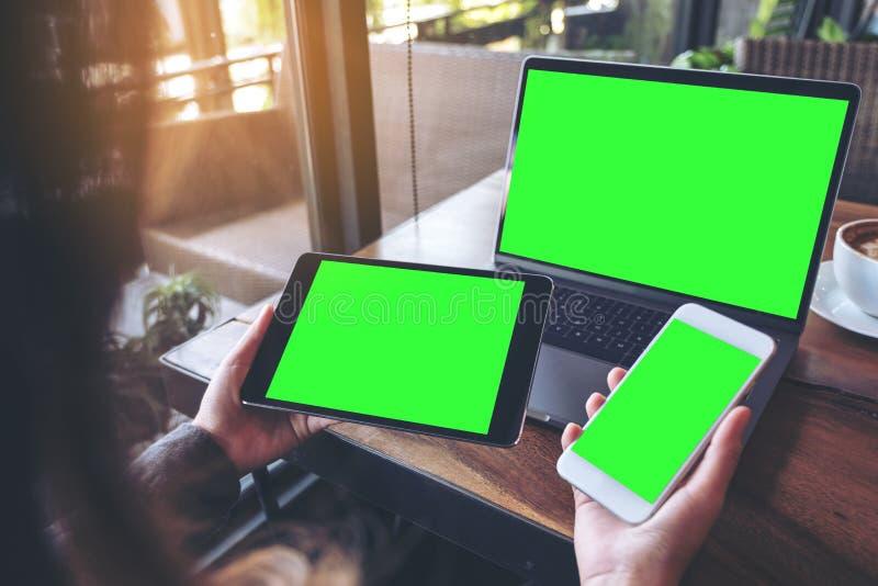 Modellbild einer Geschäftsfrau, die weißen Handy, schwarze Tablette und Laptop mit leerem grünem Schirm auf hölzernem Vorsprung d stockfotos