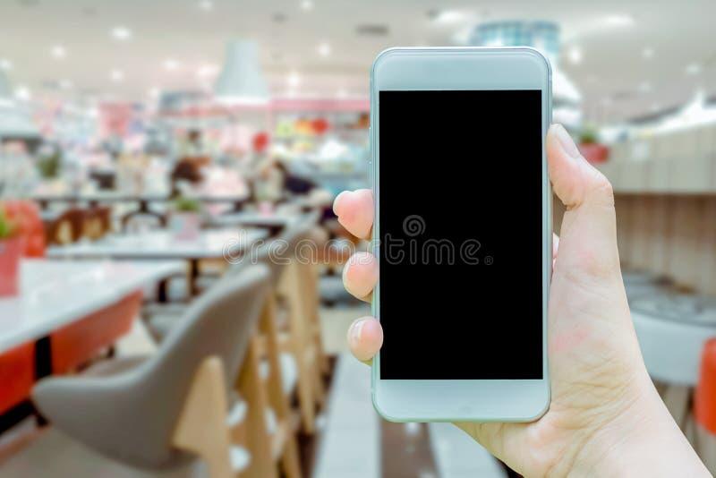 Modellbilden av den hållande vita mobiltelefonen för handen med mellanrumssvartskärmen, att att ta bildkafét är i shoppinggalleri arkivfoto