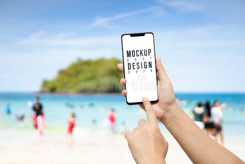 Modellbilden av ett handinnehav och visningen modren den mobila smarta telefonen av stranden i sommar med kan framme turist- och  royaltyfri bild