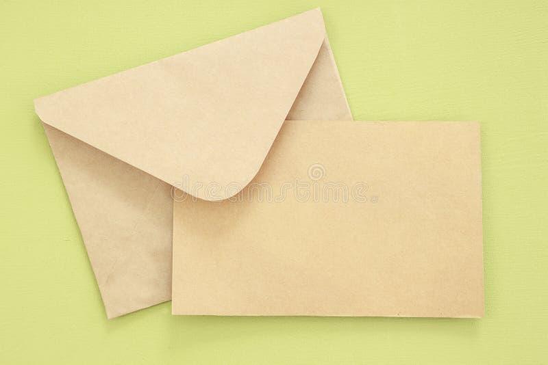 Modellbokstav eller vykort med kuvertet på grön bakgrund royaltyfri bild