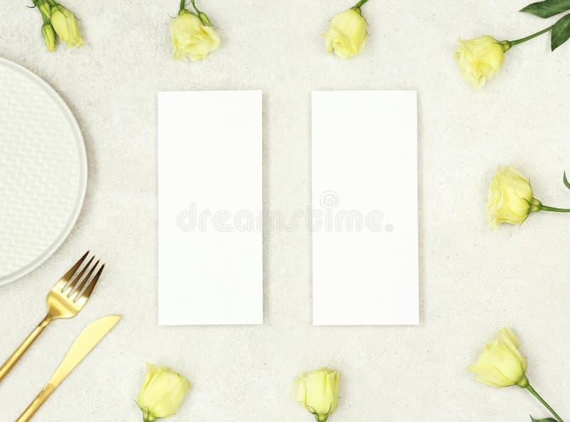 Modellbröllopmeny med blommor och guld- bestick arkivbild