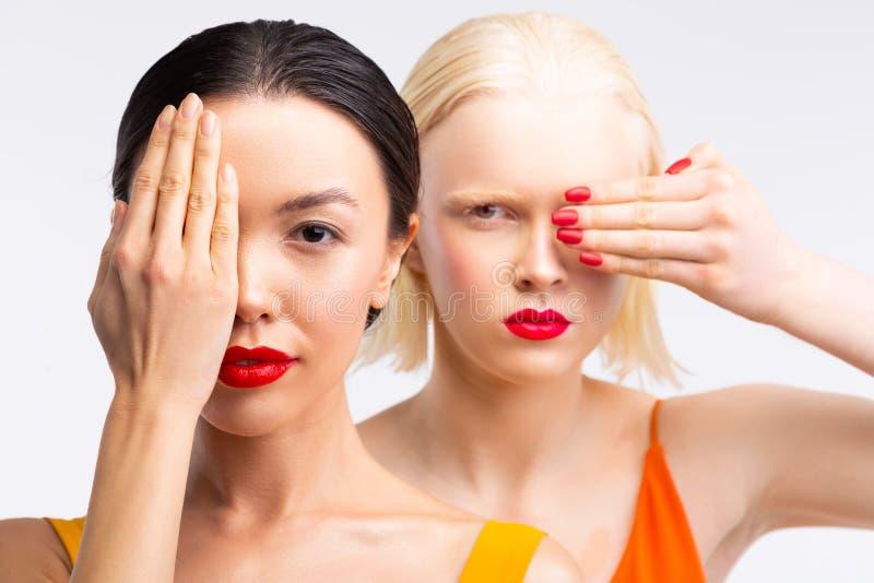 Modelle mit den hellen roten Lippen, die Teil ihres Gesichtes bei der Aufstellung verstecken stockbilder