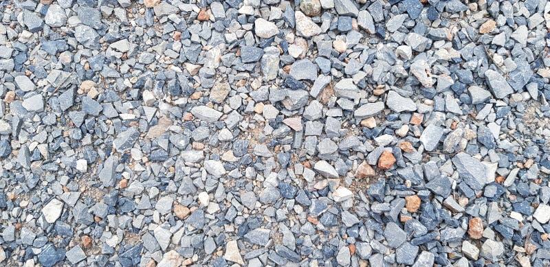 Modellen av litet grus, vaggar eller stenar på golvet för bakgrund arkivbild