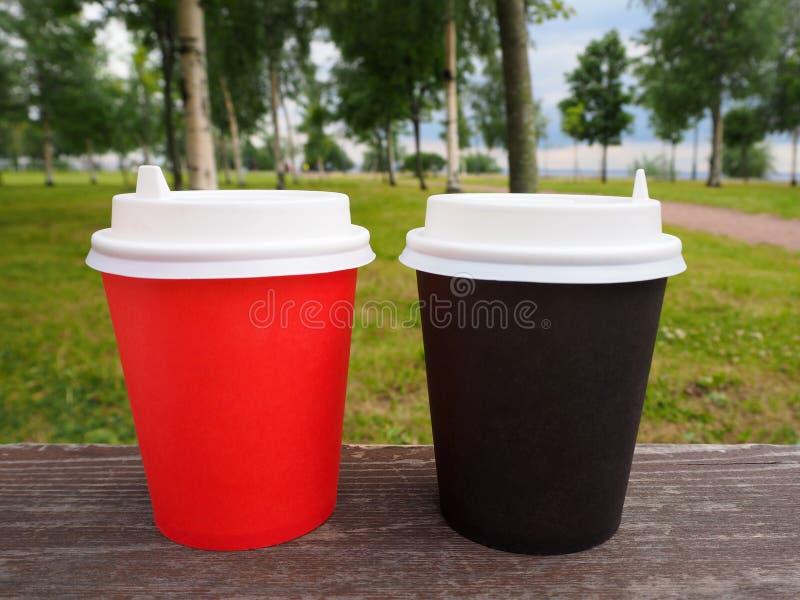 Modellen av takeaway kaffekoppar för rött och brunt papper på träyttersida på naturlig sommar parkerar bakgrund fotografering för bildbyråer