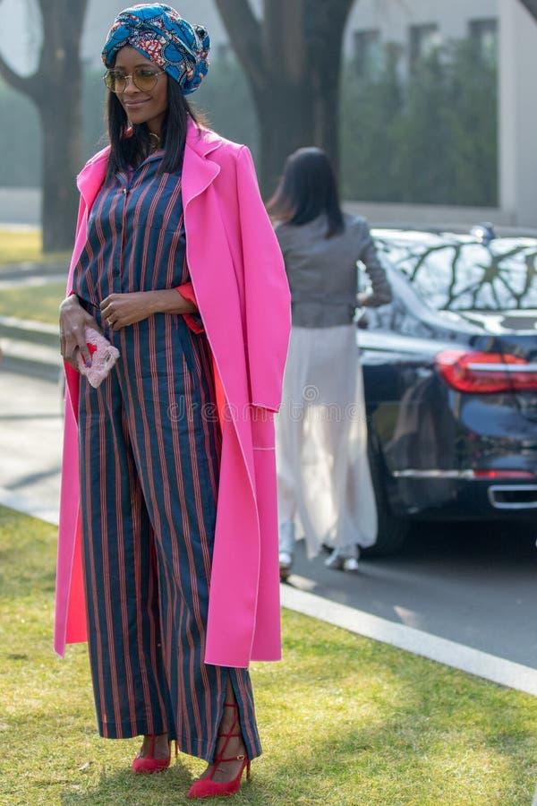 Modellen bär en lång randig klänning, en fuchsiaöverrock och en huvudbonad royaltyfri foto