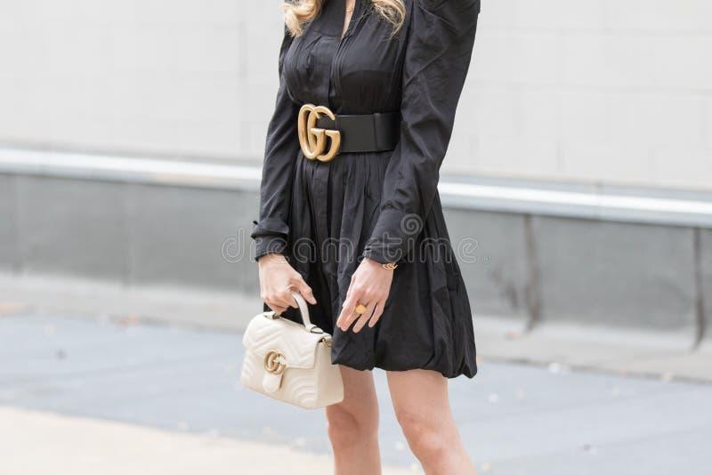 Modellen bär en svart klänning, ett slående svart Gucci-bälte och en vit Gucci-handväska arkivbild