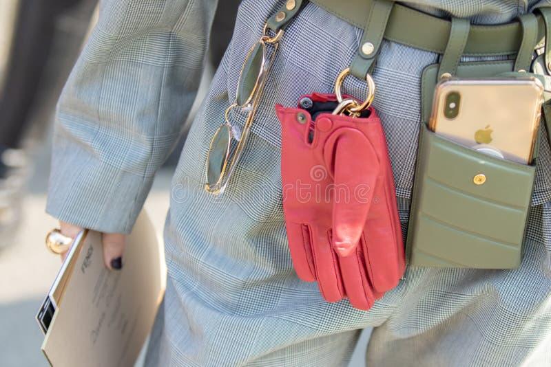 Modellen bär ett gräsplanläderbälte med fäst solglasögon, röda handskar och en telefonhållare arkivbild