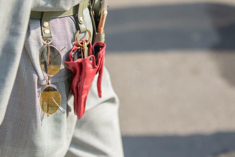 Modellen bär ett gräsplanläderbälte med fäst solglasögon, röda handskar och en telefonhållare royaltyfri fotografi
