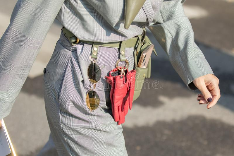 Modellen bär ett gräsplanläderbälte med fäst solglasögon, röda handskar och en telefonhållare royaltyfria foton