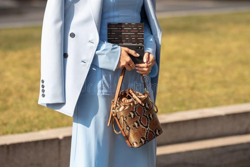 Modellen bär ett ljust - den blåa klänningen, ett blått omslag och en snakeskinhandväska royaltyfria bilder