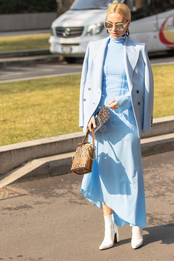 Modellen bär ett ljust - den blåa klänningen, ett blått omslag och ett par av solglasögon royaltyfri fotografi