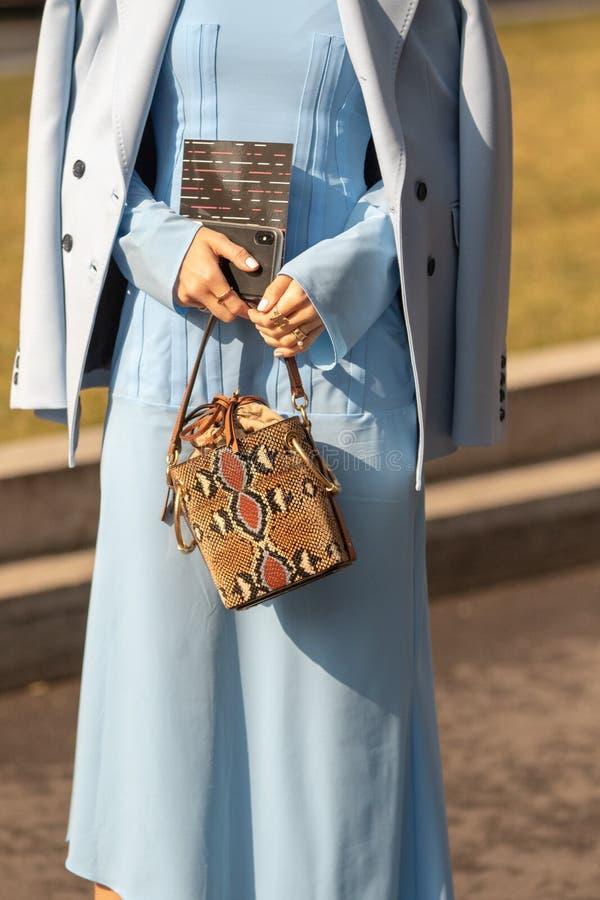 Modellen bär ett ljust - den blåa klänningen, ett blått omslag och ett par av solglasögon fotografering för bildbyråer