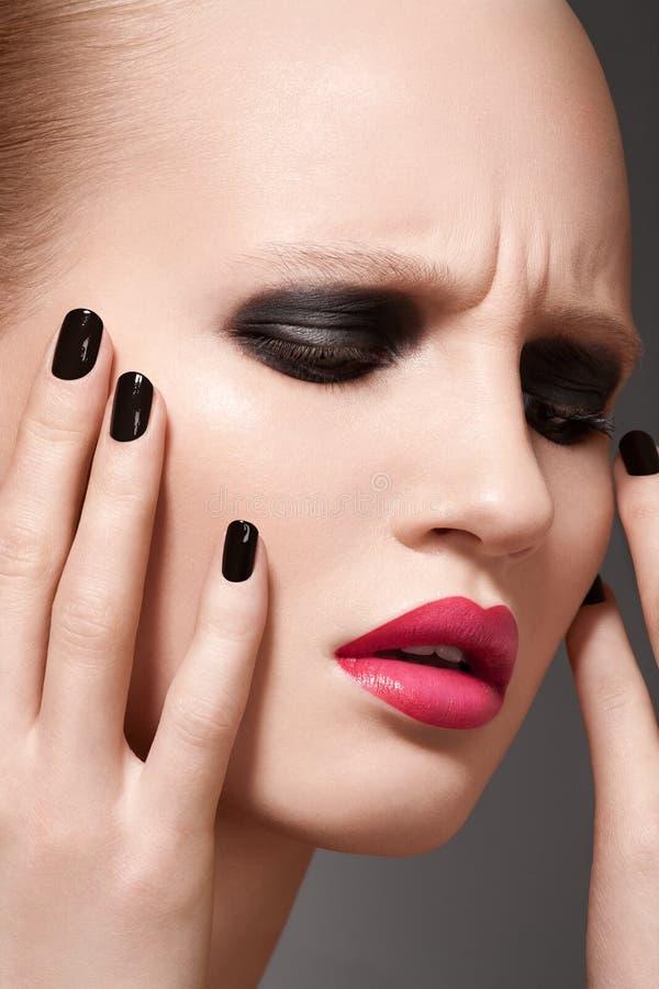 Modellen för högt mode med smink och spikar manicuren arkivfoton