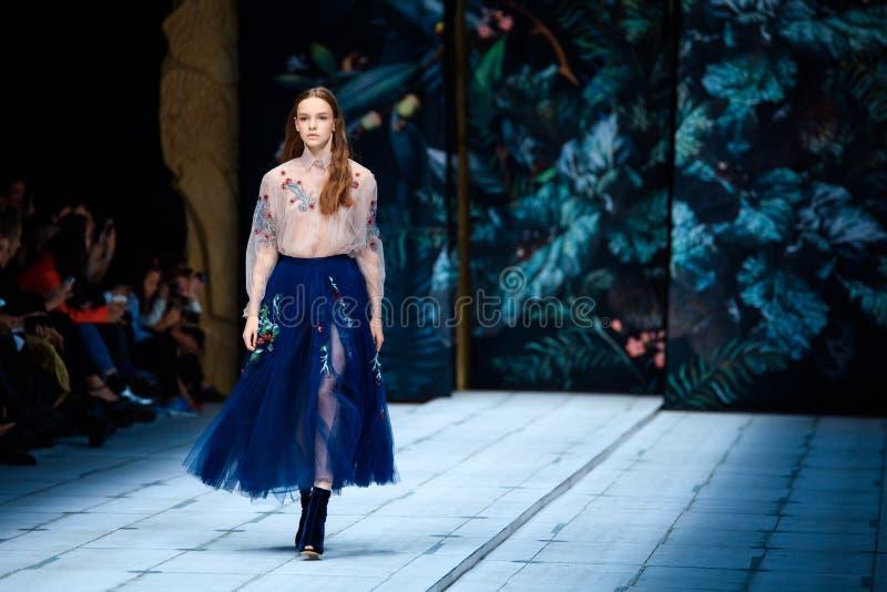 Modellen går landningsbanan för FABERLIC vid catwalken för ALENA AKHMADULLINA på Vår-sommar Mercedes-Benz Fashion Week Russia 201 royaltyfria foton
