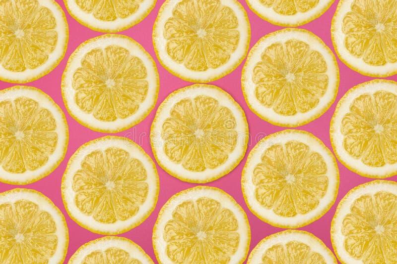 Modellen gjorde fr?n nya citronskivor p? en rosa bakgrund, den ?ver huvudet sikten som var flatlay skivad half ananas f?r bakgrun royaltyfri bild
