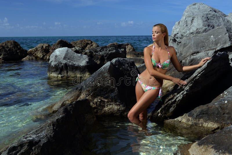 Modellen i bikinin som poserar av, vaggar framme arkivbild