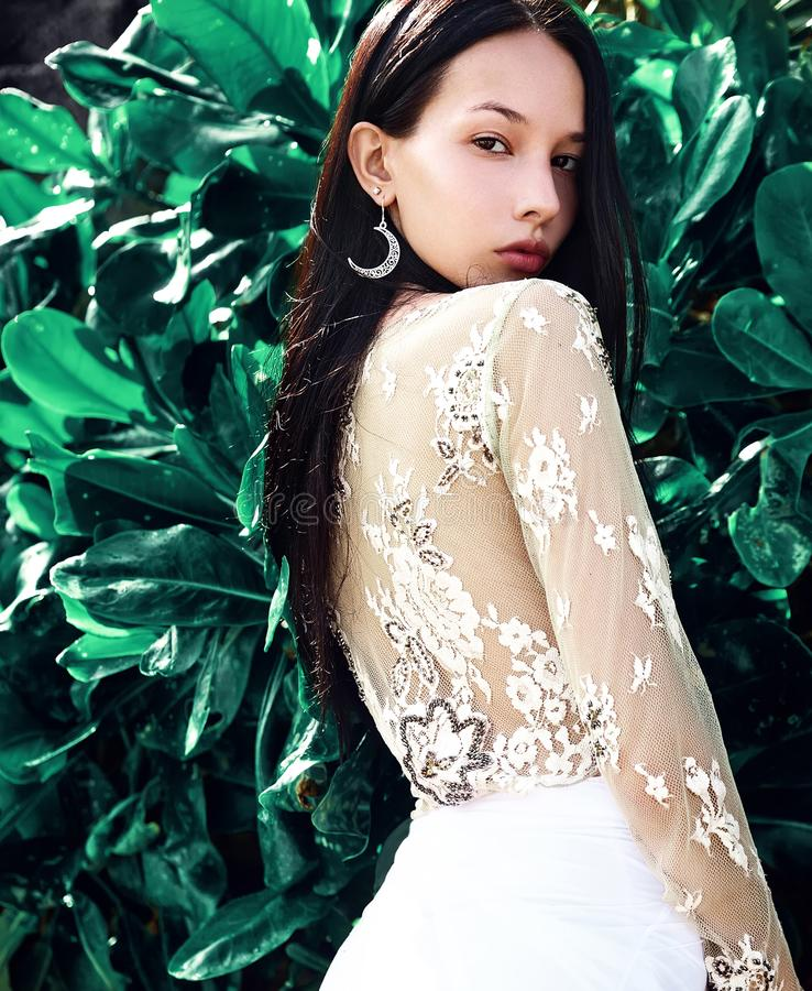 Modellen med mörkt långt hår i sned boll-ben klassiker flåsar att posera nära gröna tropiska exotiska sidor royaltyfri fotografi