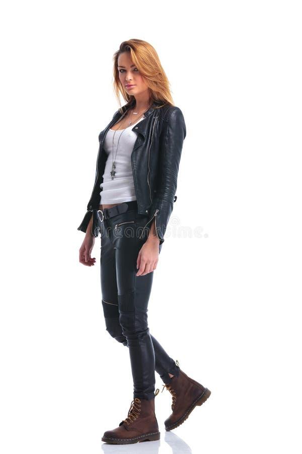Modellen poserar i läderomslag, medan gå, i studio och att se arkivfoton