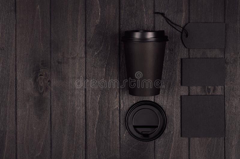 Modellen som packar för kaffeprodukter och, shoppar - den svarta papperskoppen, den tomma etiketten, kortet, brevpapper, socker p royaltyfri fotografi