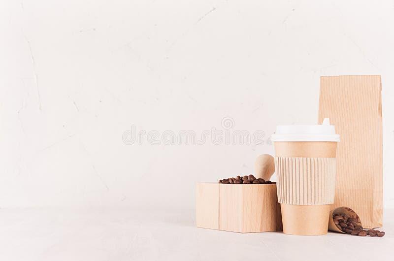 Modellen som packar för kaffeprodukter och, shoppar - koppen, paketet och mortel för brunt papper med kaffebönor på den vita trät arkivbilder