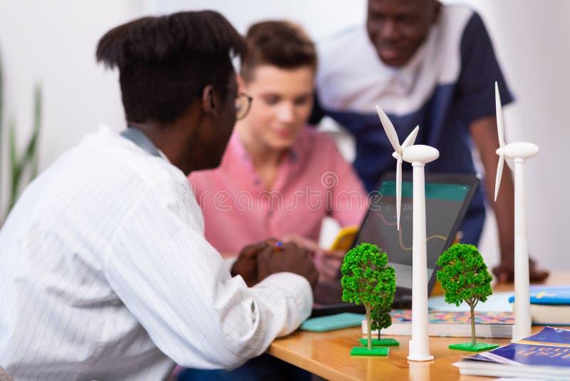 Modellen van windmolens die zich op lijst dichtbij drie slimme studenten bevinden stock foto