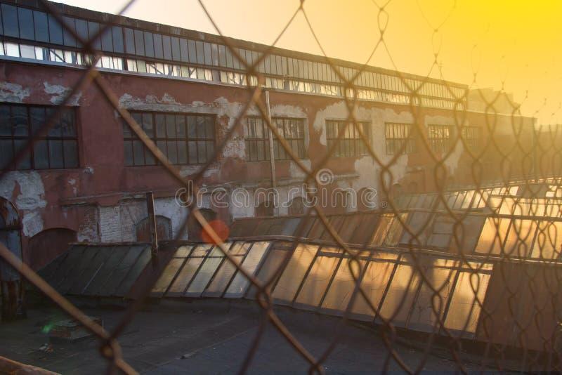 Modeller för staket för ingrepp för närbildståltråd, gammal byggnad bak rastret royaltyfri foto