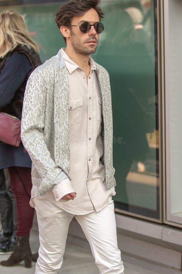 Modellera att bära ett par av byxa och en beige lång muff skjorta royaltyfria foton