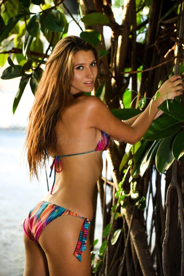 Modellera att posera som är sexigt framme av tropiskt djungelträd fotografering för bildbyråer