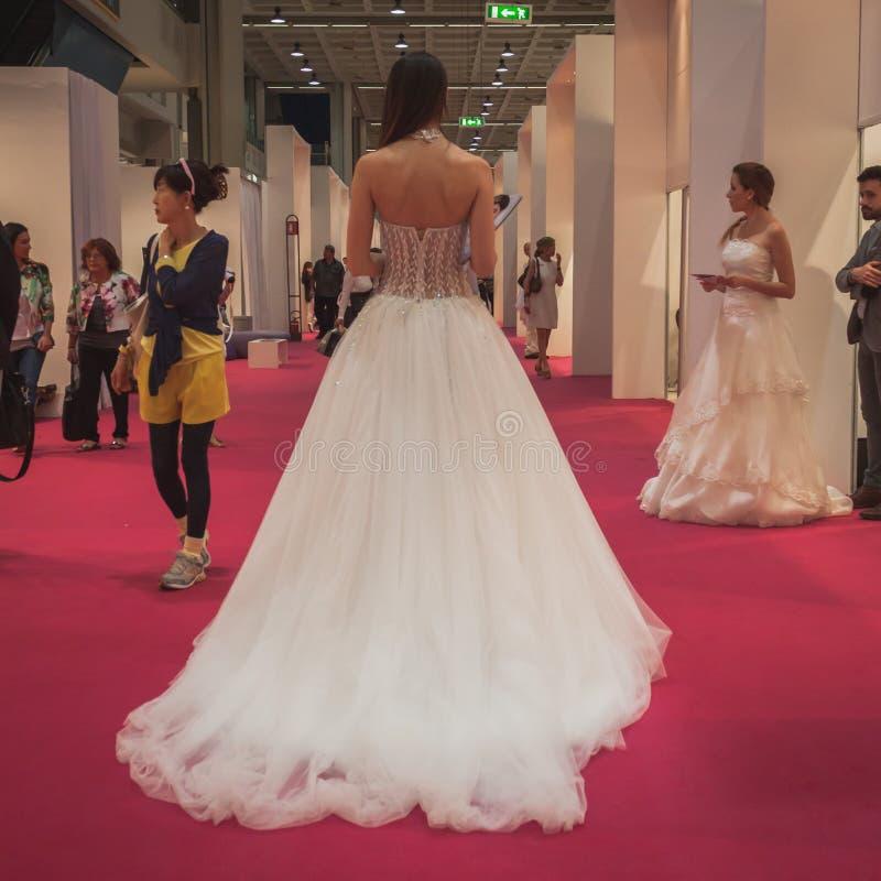 Modellera bärande bröllopsklänningar på Si Sposaitalia i Milan, Italien royaltyfri foto
