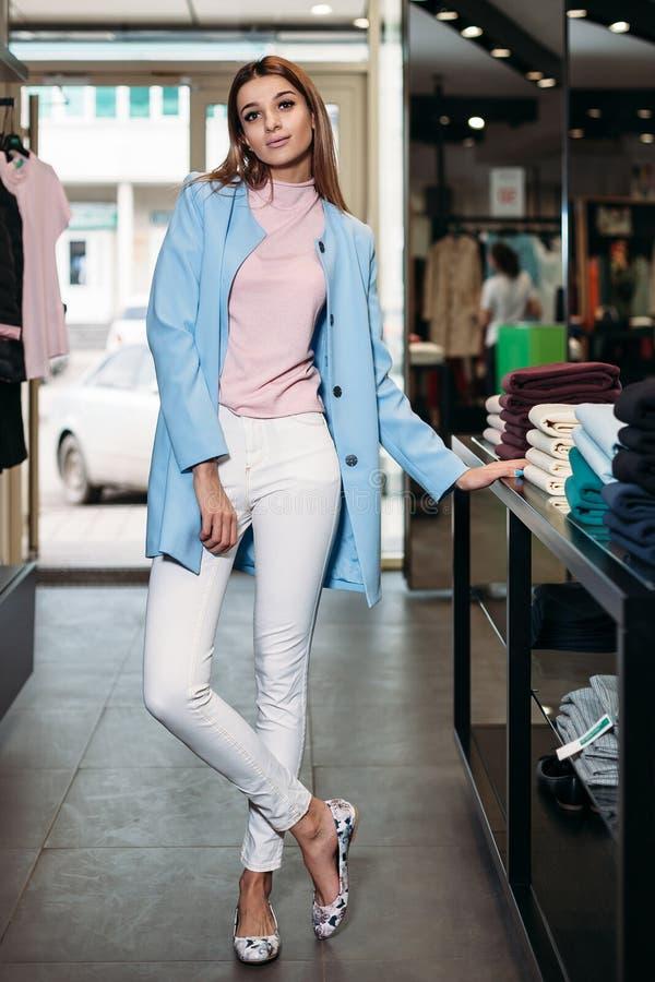 Modellera brunettflickan i stilfull kläder som poserar i klädlager, en ny trend av kläder Baner för ett bekläda lager för royaltyfria bilder