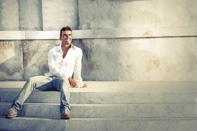 Modellera den stiliga mannen kopplat av sammanträde på momenten av vit marmor royaltyfri foto