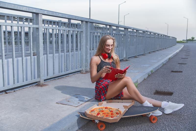 Modellera flickan med pizza tycker om röda grejer arkivbilder